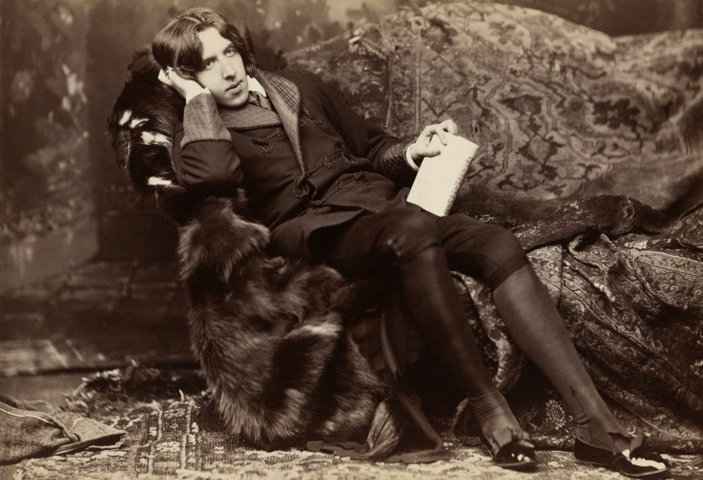 Image of Oscar Wilde sitting on a sofa
